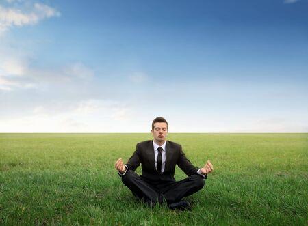 field work: Businessman meditating on a green meadow Stock Photo