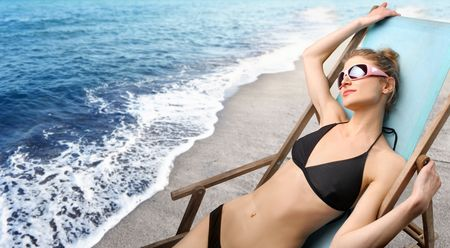 Young woman in swimsuit sunbathing at the seaside photo