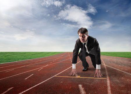 start of race: Empresario de rodillas en la parrilla de salida de una pista de atletismo
