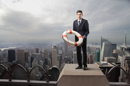 lifebelt: Businessman standing on the top of a skyscraper with a lifebelt in his hands Stock Photo