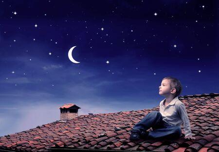 noche y luna: Ni�o sentado en una azotea y mirando la Luna  Foto de archivo
