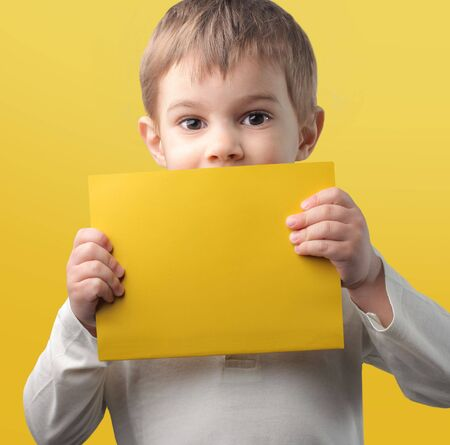 teaches: Child holding a yellow paper sheet Stock Photo