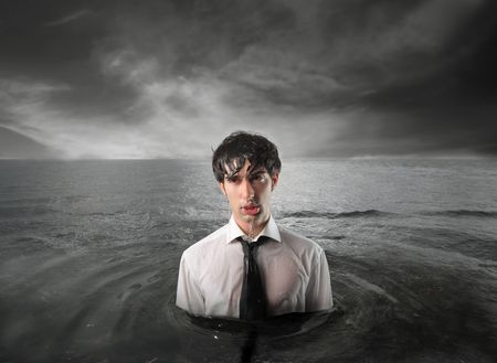 drown: Wet businessman standing in the water with stormy sky on the background Stock Photo