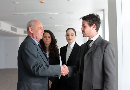 accordance: Young businessman and senior manager shaking hands with two businesswomen on the background