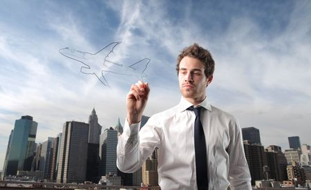 Businessman drawing an airplane with cityscape on the background photo