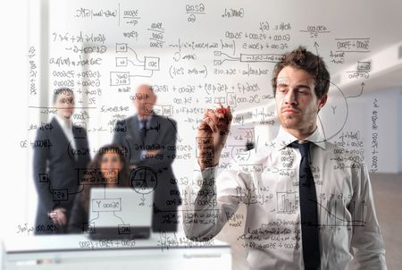 budgets: Young businessman writing some statistics with group of business people on the background Stock Photo