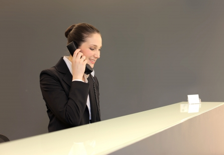 Smiling receptionist answering to telephone photo