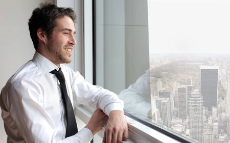 company: Smiling young businessman looking out of the window