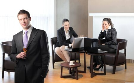 Businessman with glass of wine with two smiling businesswomen sitting on the background photo