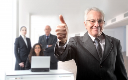 Senior businessman with thumbs up and business people on the background