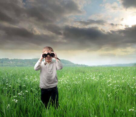 using binoculars: Child on a green meadow using binoculars