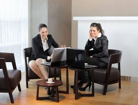 business lounge: Two smiling businesswomen sitting in front of laptops in a lounge Stock Photo
