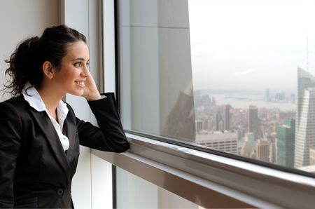 office window view: Smiling businesswoman looking out of a window