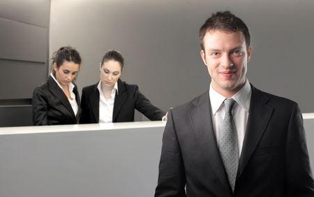 manager: L�chelnd Gesch�ftsmann mit zwei Rezeptionschefs auf dem Hintergrund Lizenzfreie Bilder