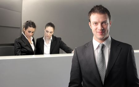 reception hotel: Smiling businessman with two receptionists on the background