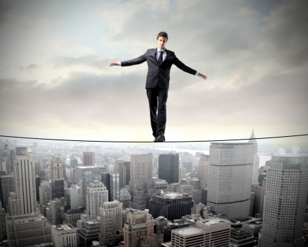 scared man: Businessman in equilibrium on a rope over a cityscape Stock Photo