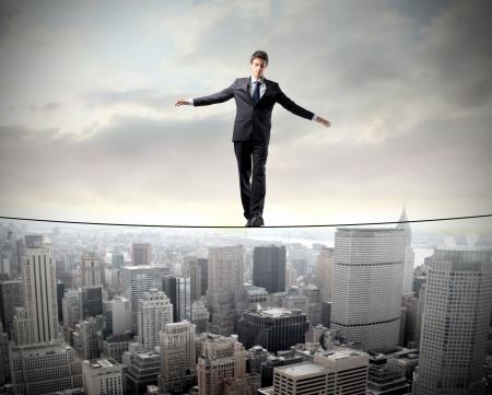 Empresario en equilibrio sobre una cuerda sobre un paisaje urbano