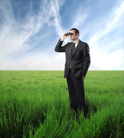 binoculars: Businessman on a green meadow using binoculars