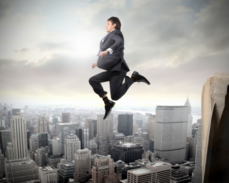 risky business: Businessman jumping from a skyscraper