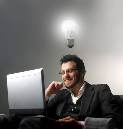 bulb idea: Smiling businessman sitting in front of a laptop and having an idea