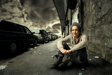 street fashion: Young woman sitting on a city street