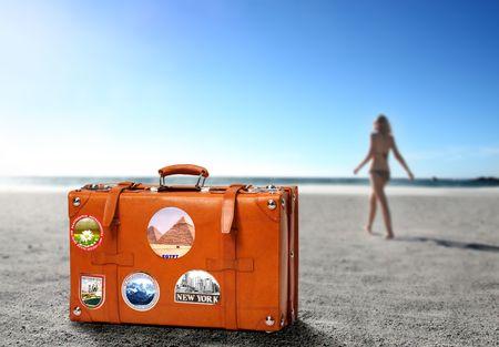 Valigia e bella donna in costume da bagno sullo sfondo
