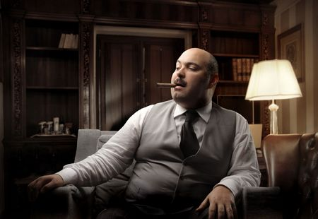 advocate: Fat man sitting on an armchair and smoking a cigar Stock Photo