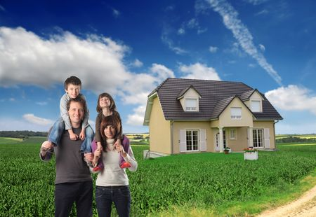 Happy family with big house on green lawn on the background