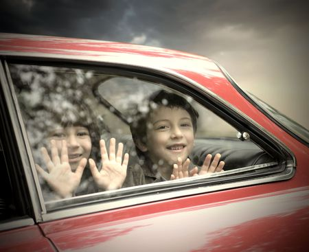 Two smiling children sitting in a car photo