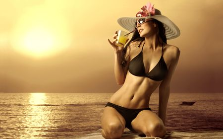 girl drinking water: Beautiful woman in swimsuit drinking a cocktail Stock Photo