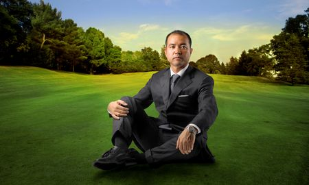 Japanese businessman sitting on a green lawn photo