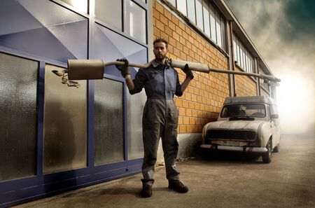 mechanician: Mechanician carrying a tool in front of a car garage Stock Photo