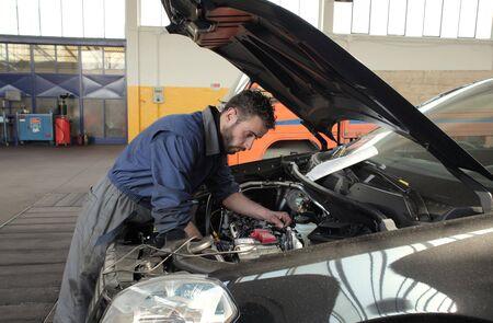 mechanician: Mechanician working a car engine Stock Photo