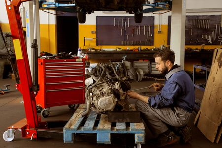 mechanician: Mechanician repairing a car engine