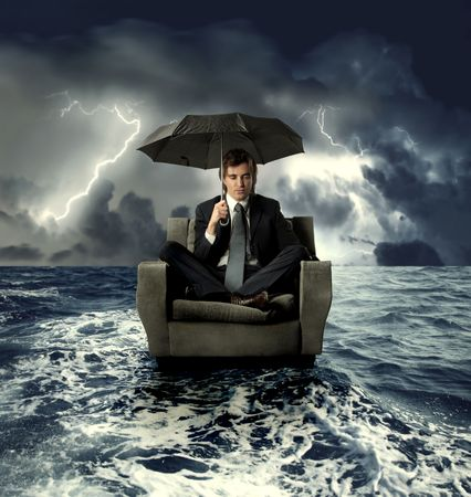 business failure: Businessman sitting under an umbrella on a sofa with sea on the background