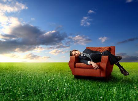 tired businessman: Tired businessman sleeping on a sofa on a green meadow