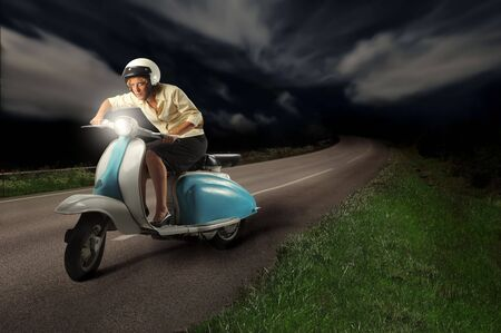moped: Woman riding a scooter on a street Stock Photo