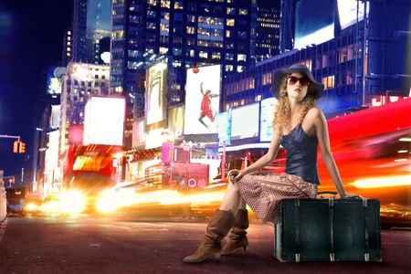 time drive: Woman sitting on a suitcase with times square on the background Stock Photo