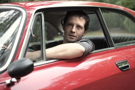 the car window: Young attractive man driving a car Stock Photo
