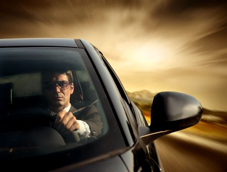 Driving a car: Businessman wearing sunglasses while driving his car Stock Photo
