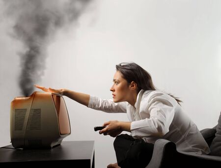 overheating: Amazed woman sittin gin front of an overheating television