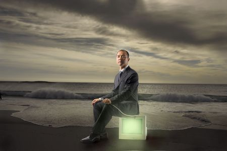 Japanese businessman sitting on a cube with light inside photo