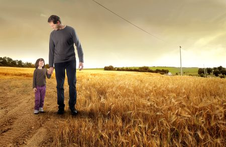 baby corn: Father hand in hand with his daughter on a field Stock Photo