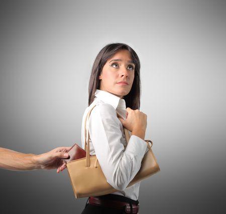 ladron: Mano de hombre robando una billetera de bolso de una mujer