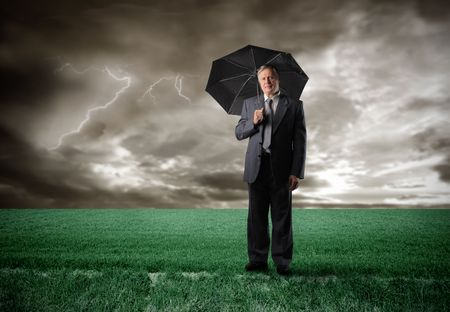 economic issues: Senior businessman under an umbrella