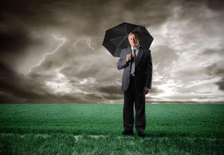 economic issues: Senior businessman under an umbrella