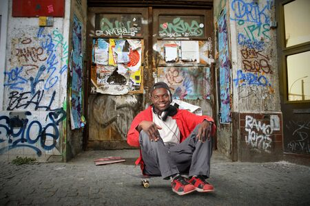 Smiling black man sitting on a city street and listening to music photo