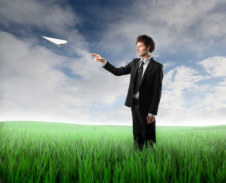 Businessman throwing a plane made of paper on a green meadow photo