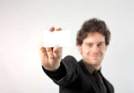 Smiling businessman showing a card Stock Photo - 7083144