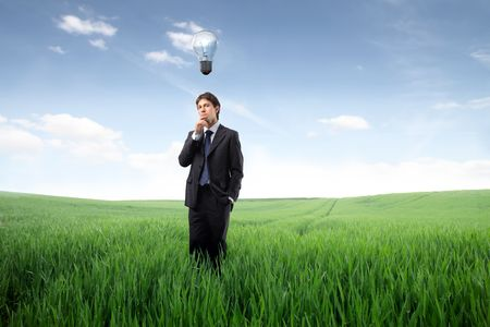 Businessman standing on a green meadow and having an idea